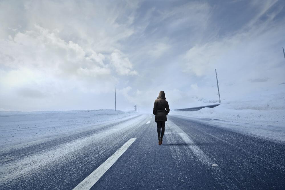 woman walking away on road